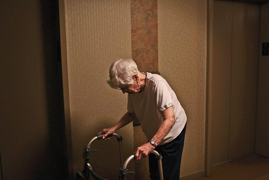 Eleanor Hammer, whose husband David fell and fractured his femur while she was away, waits for the elevator at her apartment building in San Francisco, July 10, 2014. RAMIN RAHIMIAN/THE NEW YORK TIMES/REDUX