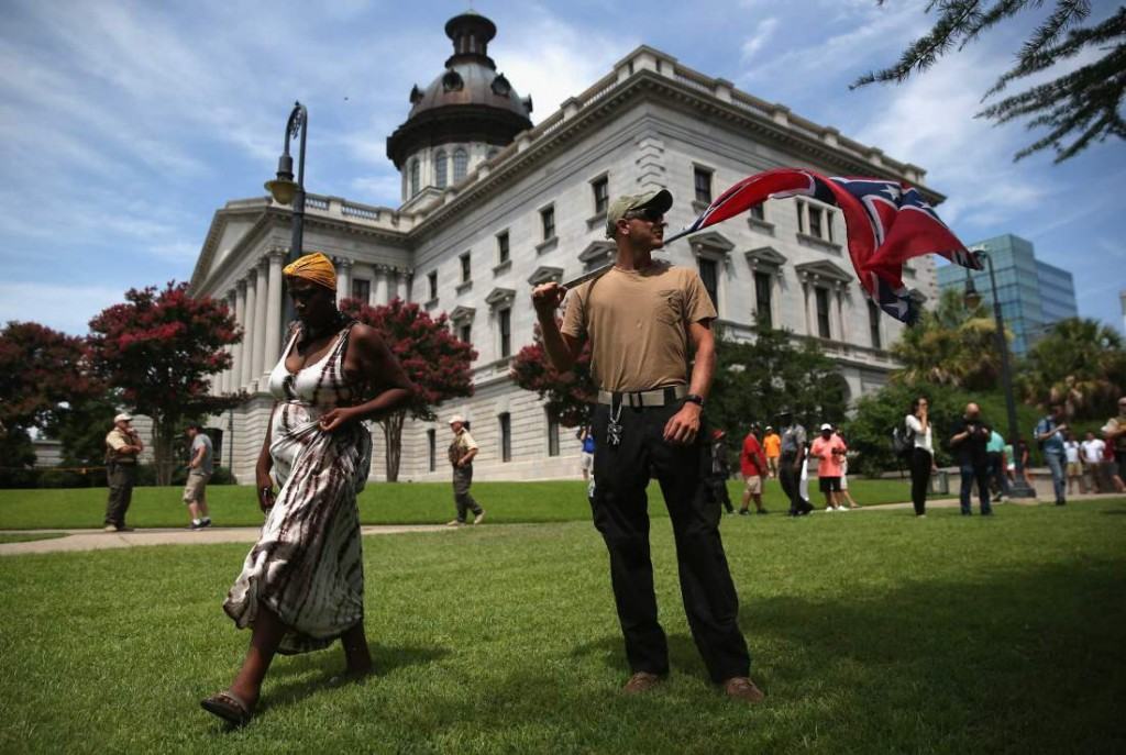 COLUMBIA, SC - JULY 18:  A man holds a Confederate flag on the state house grounds on July 18, 2015 in Columbia, South Carolina. The Ku Klux Klan and opposing groups were scheduled to hold competing rallies at the state house in the afternoon and the government issued a weapons ban around the state house as a precautionary measure.  (Photo by John Moore/Getty Images) *** BESTPIX ***