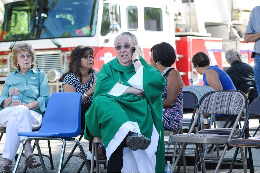 While waiting in a staging area, Holy Cross Catholic Church Pastor John Anderson tries to get in touch with other local churches to warn them of the two explosions that occurred Sunday morning and to be vigilant. (Robin Zielinski Sun-News)