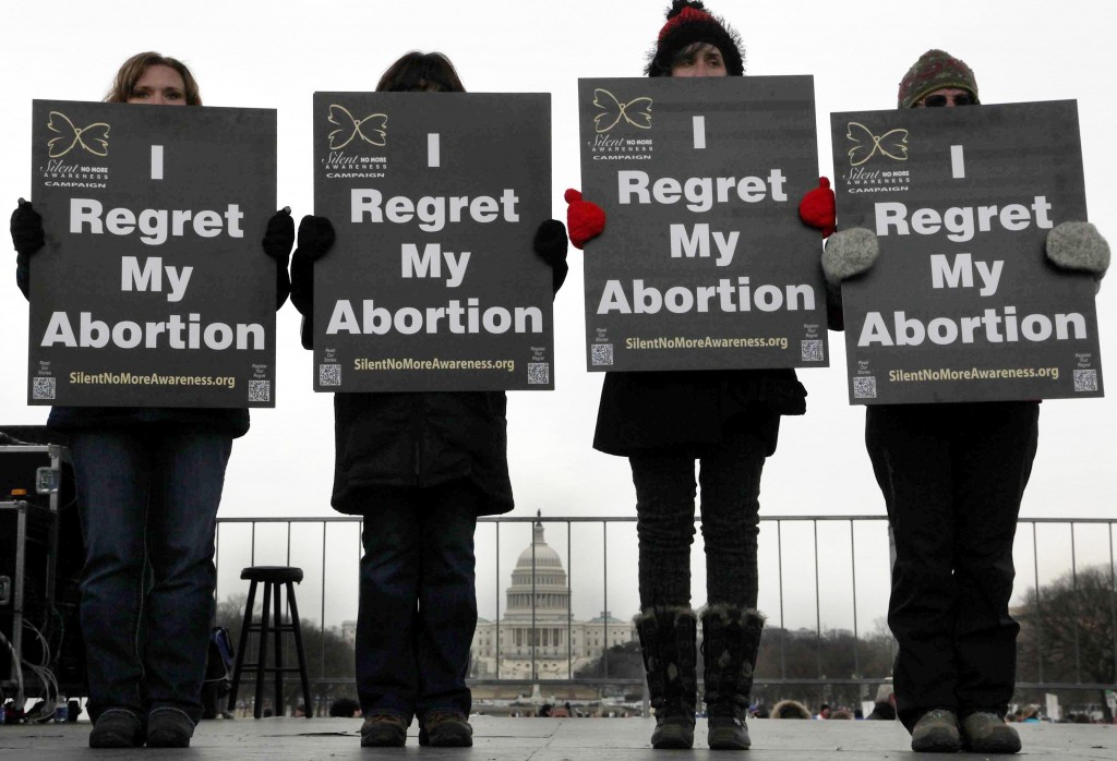 """Activists hold signs reading """"I regret my abortion"""" during the annual March for Life rally on the National Mall in Washington Jan. 25. Pope Benedict XVI expressed support for anti-abortion demonstrators marking the 40th anniversary of the Supreme Court's Roe v. Wade ruling that legalized abortion across the nation. (CNS photo/Jonathan Ernst, Reuters) (Jan. 25, 2013) See MARCH-SPEECHES, MARCH COLOR Jan. 25, 2013."""