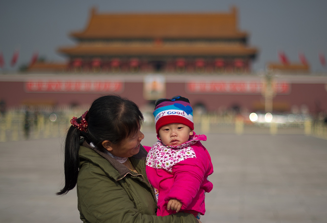 A woman holds a child on Tiananmen Square in Beijing on November 9, 2012. The week-long congress, held every five years, will end with a transition of power to Vice President Xi Jinping, who will govern for the coming decade amid growing pressure for reform of the communist regime's iron-clad grip on power. AFP PHOTO / Ed Jones        (Photo credit should read Ed Jones/AFP/Getty Images)