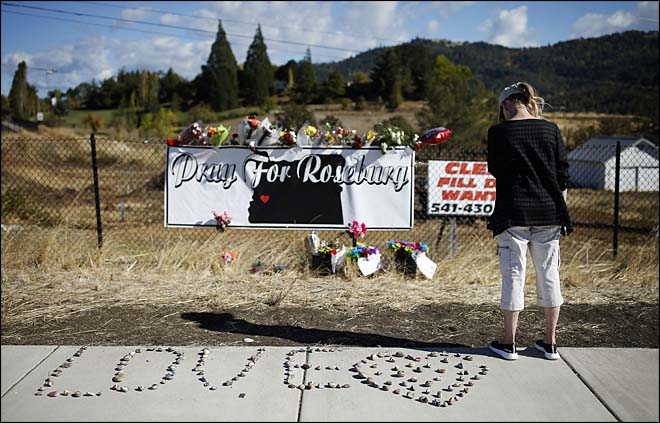 A woman visits a makeshift memorial near the road leading to Umpqua Community College, Saturday, Oct. 3, 2015, in Roseburg, Ore. Armed with multiple guns, Chris Harper Mercer walked in a classroom at the community college, Thursday, and opened fire, killing several and wounding several others. (AP Photo/John Locher)