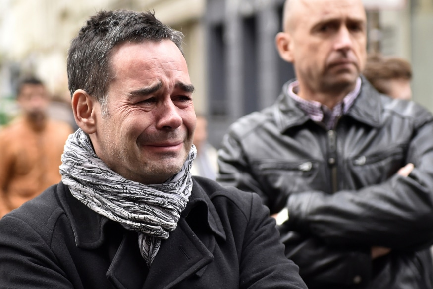 TOPSHOTS People react near the cafe 'La Belle Equipe' at the Rue de Charonne in Paris on November 14, 2015, following a series of coordinated attacks in and around Paris late Friday. At least 128 people were killed in the Paris attacks on the evening of November 13, with 180 people injured, 80 of them seriously, police sources told AFP. AFP PHOTO / LOIC VENANCE