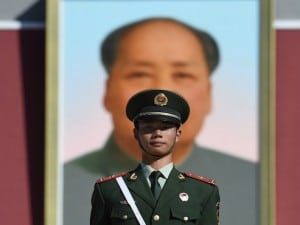 A paramilitary policeman stands guard in front of the portrait of late communist leader Mao Zedong on Tiananmen Gate in Beijing on China's National Day, October 1, 2015. China is marking the 66th anniversary of Mao's founding of the People's Republic of China on October 1, 1949. AFP PHOTO / GREG BAKER / AFP / GREG BAKER