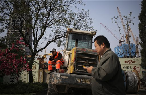 In this  Monday, April 11, 2016 photo, a man walks past a worker smoking on a bulldozer parked by a construction site at the Central Business District in Beijing. China will remain the main driver of growth in Asia this year despite its prolonged slowdown, helped by sustained expansions in other developing countries in the region, the World Bank said Monday. (AP Photo/Andy Wong, File)