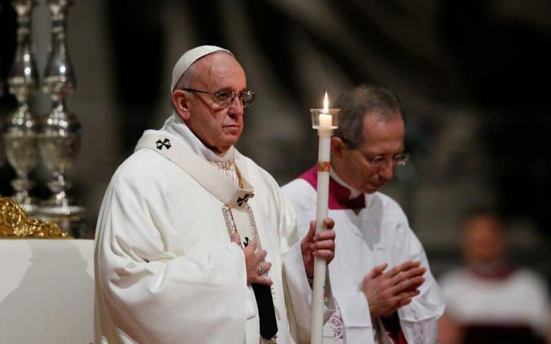 Pope Francis holds a candle as he celebrates a Mass with religious in St Peter's Basilica in February (CNS)