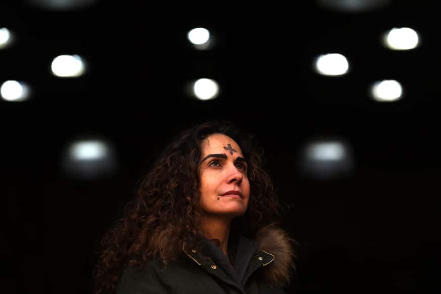 A Lebanese Christian woman stands in front of her shop, her forehead marked with an ash cross, as she marks Ash Monday in Beirut on February 08, 2016.  Middle Eastern Catholic churches mark the first day of lent in which priests make the sign of the cross with ashes on the forehead of their parishioners.  / AFP / PATRICK BAZ