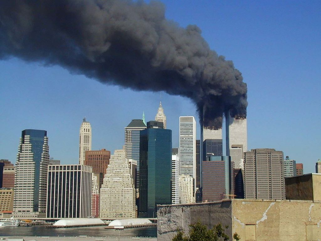 Plumes of smoke billow from the World Trade Center towers in Lower Manhattan, New York City, after a Boeing 767 hits each tower during the September 11 attacks - CC BY 2.0